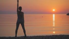 Den unga kvinnan gör några övningar på stranden stock video