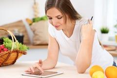 Den unga kvinnan gör online-shopping vid den minnestavladatoren och kreditkorten Royaltyfria Foton