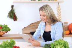 Den unga kvinnan gör online-shopping vid den minnestavladatoren och kreditkorten Hemmafru funnit nytt recept för att laga mat in Royaltyfria Foton