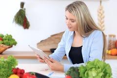 Den unga kvinnan gör online-shopping vid den minnestavladatoren och kreditkorten Hemmafru funnit nytt recept för att laga mat in Arkivfoto