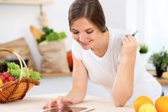 Den unga kvinnan gör online-shopping vid den minnestavladatoren och kreditkorten Hemmafrun grundar det nya receptet för att laga  Arkivbilder