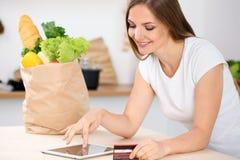 Den unga kvinnan gör online-shopping vid den minnestavladatoren och kreditkorten Hemmafrun grundar det nya receptet för att laga  Arkivbild