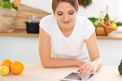 Den unga kvinnan gör online-shopping vid den minnestavladatoren och kreditkorten Hemmafrun grundar det nya receptet för att laga  Royaltyfri Bild