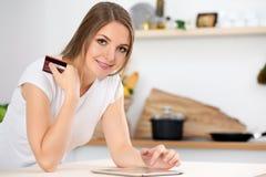 Den unga kvinnan gör online-shopping vid den minnestavladatoren och kreditkorten Hemmafrun grundar det nya receptet för att laga  Royaltyfri Foto
