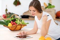 Den unga kvinnan gör online-shopping vid den minnestavladatoren och kreditkorten Hemmafrun grundar det nya receptet för att laga  Royaltyfria Bilder