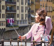 Den unga kvinnan gör selfies på den Ponte Vecchio bron i Florence - FLORENCE/ITALIEN - SEPTEMBER 12, 2017 Arkivbild