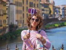 Den unga kvinnan gör selfies på den Ponte Vecchio bron i Florence - FLORENCE/ITALIEN - SEPTEMBER 12, 2017 Arkivfoto