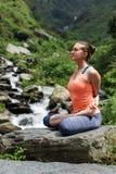 Den unga kvinnan gör yogaoudoors på vattenfallet Arkivbild