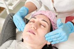 Den unga kvinnan g?r yrkesm?ssig ansikts- massage i sk?nhetsalongen arkivbilder