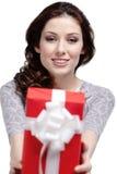 Den unga kvinnan ger en gåva Arkivbilder