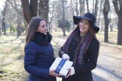 Den unga kvinnan ger hennes vän en gåva Arkivfoto
