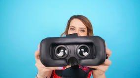 Den unga kvinnan ger virtuell verklighetskyddsglasögon lager videofilmer