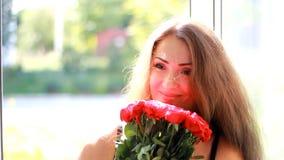 Den unga kvinnan ges en bukett av röda rosor Födelsedag Beröm gåva lager videofilmer