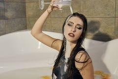 Den unga kvinnan häller mjölkar på henne Kvinna med suddig makeup arkivbild
