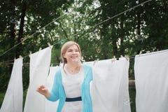 Den unga kvinnan hänger vita rena ark i trädgården Inhemskt ansvar En kvinna ler och fångar såpbubblor stort royaltyfria foton