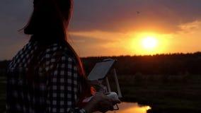 Den unga kvinnan håller en panel för att kontrollera hennes surr på solnedgången i slo-mo arkivfilmer