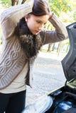 Den unga kvinnan har en bilsammanbrott Arkivfoton