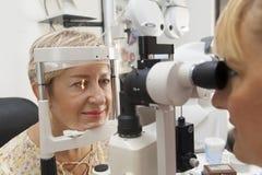 Den unga kvinnan har en läkarundersökning på optometrikern Arkivbilder