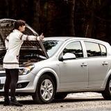 Den unga kvinnan har ett problem med hennes bil på vägen Arkivfoton