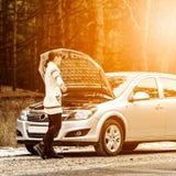 Den unga kvinnan har ett problem med hennes bil på vägen Fotografering för Bildbyråer
