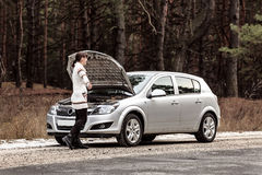 Den unga kvinnan har ett problem med hennes bil på vägen Royaltyfria Bilder