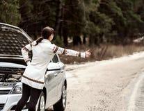 Den unga kvinnan har ett problem med hennes bil på vägen Arkivbilder