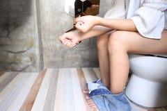 Den unga kvinnan har förstoppning eller hemorrojder som sitter på toalett, H arkivfoto
