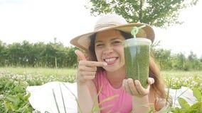 Den unga kvinnan har gyckel i parkera och dricker gröna smoothies lager videofilmer