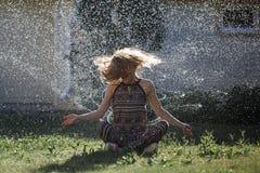 Den unga kvinnan har gyckel med en sprej av vatten arkivfoto