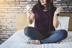 Den unga kvinnan har gyckel på sovrum, i att tycka om lyssna musikintelligensen royaltyfria bilder
