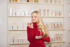 Den unga kvinnan har valt dofter i ett apotek Arkivfoton