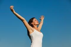 Den unga kvinnan, hennes framsida uppåt som tycker om solen - lagerföra bilden Royaltyfri Fotografi