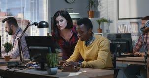 Den unga kvinnan hjälper kollegan