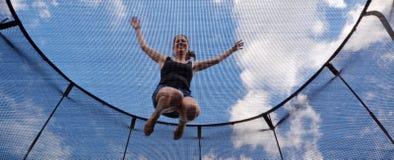 Den unga kvinnan hoppar på en trampolin Arkivfoto