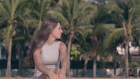 Den unga kvinnan i åtsittande sommardressing mot gräsplan gömma i handflatan arkivfilmer