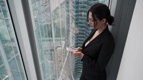 Den unga kvinnan i affärskläder använder en smartphone, medan stå på ett högt golv av en skyskrapa arkivfilmer