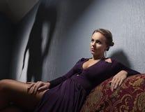 Den unga kvinnan i aftonklänning och gärningsman`en s skuggar royaltyfri foto