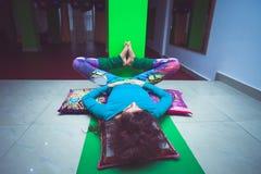 Den unga kvinnan, i att koppla av för yoga, poserar med ben upp väggen Arkivbilder