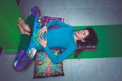 Den unga kvinnan, i att koppla av för yoga, poserar med ben upp väggen Royaltyfri Fotografi