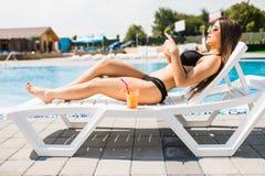 Den unga kvinnan i baddräkt som kopplar av med coctailen på schäslong och, använder hennes telefon för att smsa unga vuxen männis arkivbilder