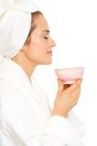 Den unga kvinnan i badrock som tycker om, kuper av tea Royaltyfria Foton