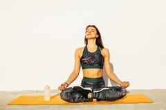 Den unga kvinnan i berget poserar, medan g?ra yogayttersidan royaltyfria bilder