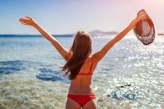 Den unga kvinnan i bikini öppnar armar som känner sig lyckliga och fria på stranden vid Röda havet resa och semesterbegrepp royaltyfri foto