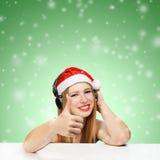 Den unga kvinnan i den Santa Claus hatten och hörlurar med tummar up ges Royaltyfri Foto