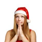 Den unga kvinnan i den santa hatten gör en önska Arkivfoto