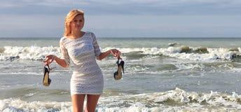 Den unga kvinnan i den vita klänningen som rymmer hans skor för höga häl som står på stranden med havet, vinkar Arkivfoto