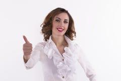 Den unga kvinnan i den vita skjortavisningen tummar upp Royaltyfria Bilder