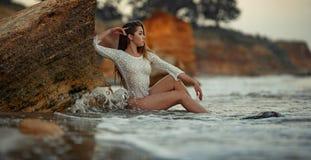 Den unga kvinnan i den vita spets- klänningen sitter vaggar nära vid havet Arkivfoton