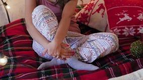 Den unga kvinnan i en julinre sitter på en säng arkivfilmer