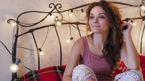 Den unga kvinnan i en julinre sitter på en säng stock video